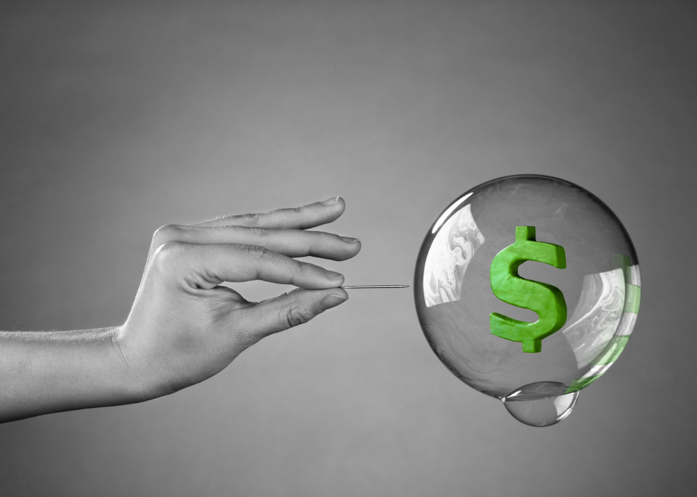 A hand about to burst a money bubble with a pin. Metaphor for an economic or financial bubble crisis.