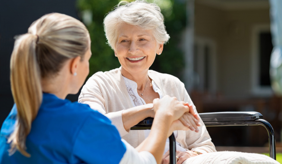 Smiling senior patient sitting on wheelchair with nurse supporting her. Doctor looking at elderly patient on a wheelchair in the garden. Nurse holding hand of mature woman outside pension home.