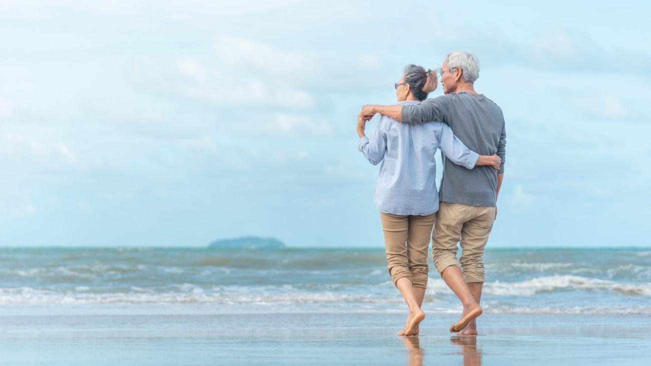 Happy senior couple on the beach. Exotic luxury resort.back view.