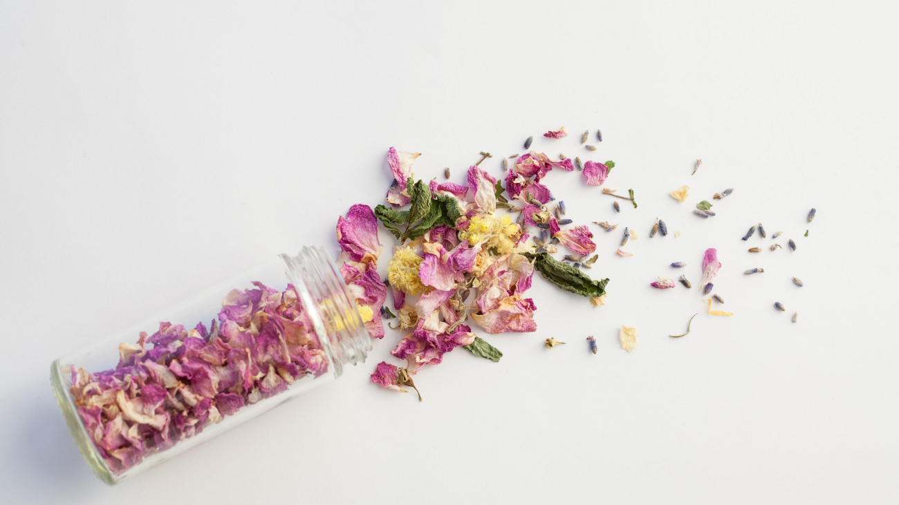 Opened glass bottle with dry mix of flowers on white background