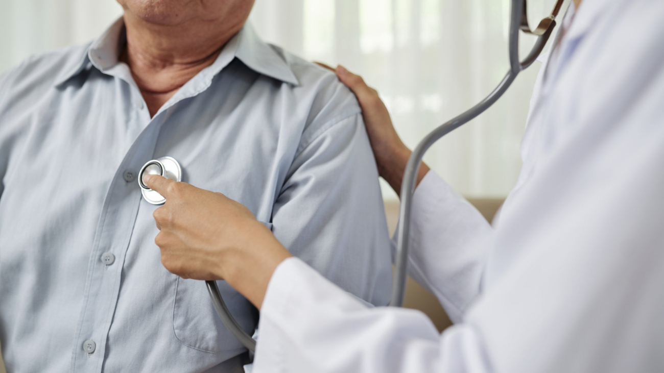Close-up of female doctor in white coat listening to breathe of senior man during his visit at hospital