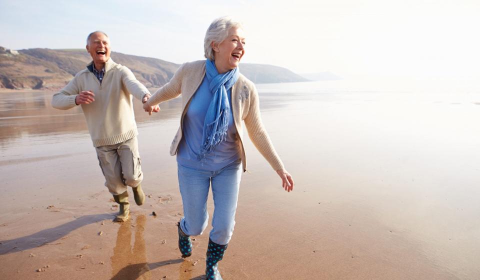 Senior Couple Running Along Winter Beach Laughing