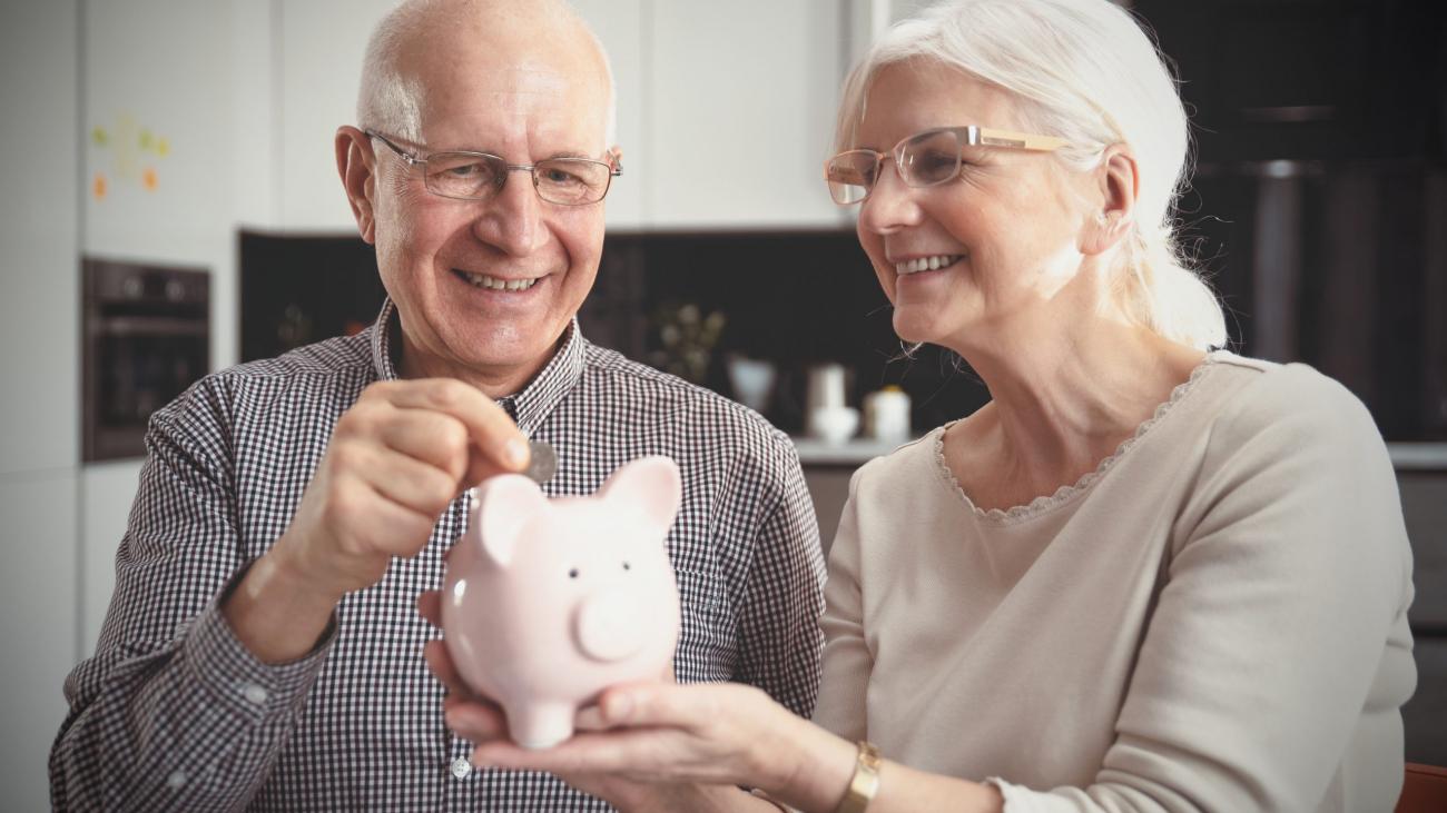 Senior couple puts the coin into the piggybank. Retirement savings concept.