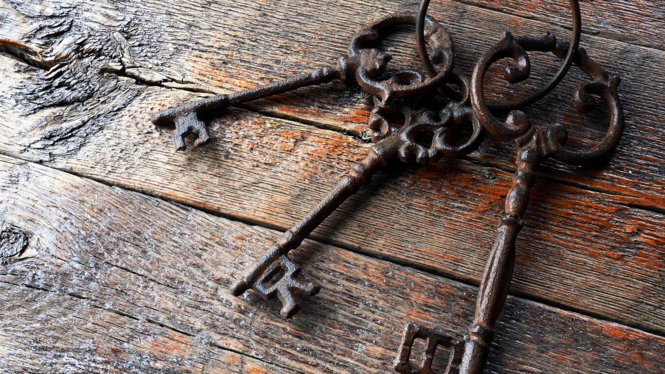 A top view image of three antique keys on a wooden table top.