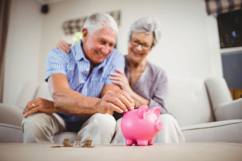 Senior man sitting with woman on sofa and putting coins in piggy bank