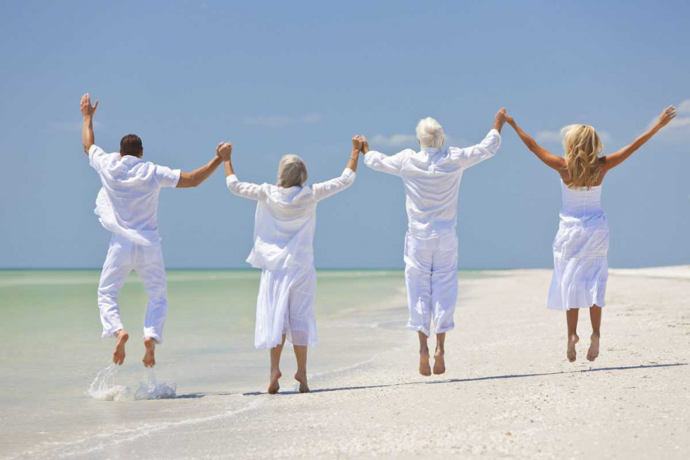 Rear view of four people, two seniors, couples or family generations, holding hands, having fun and jumping in celebration on a tropical beach