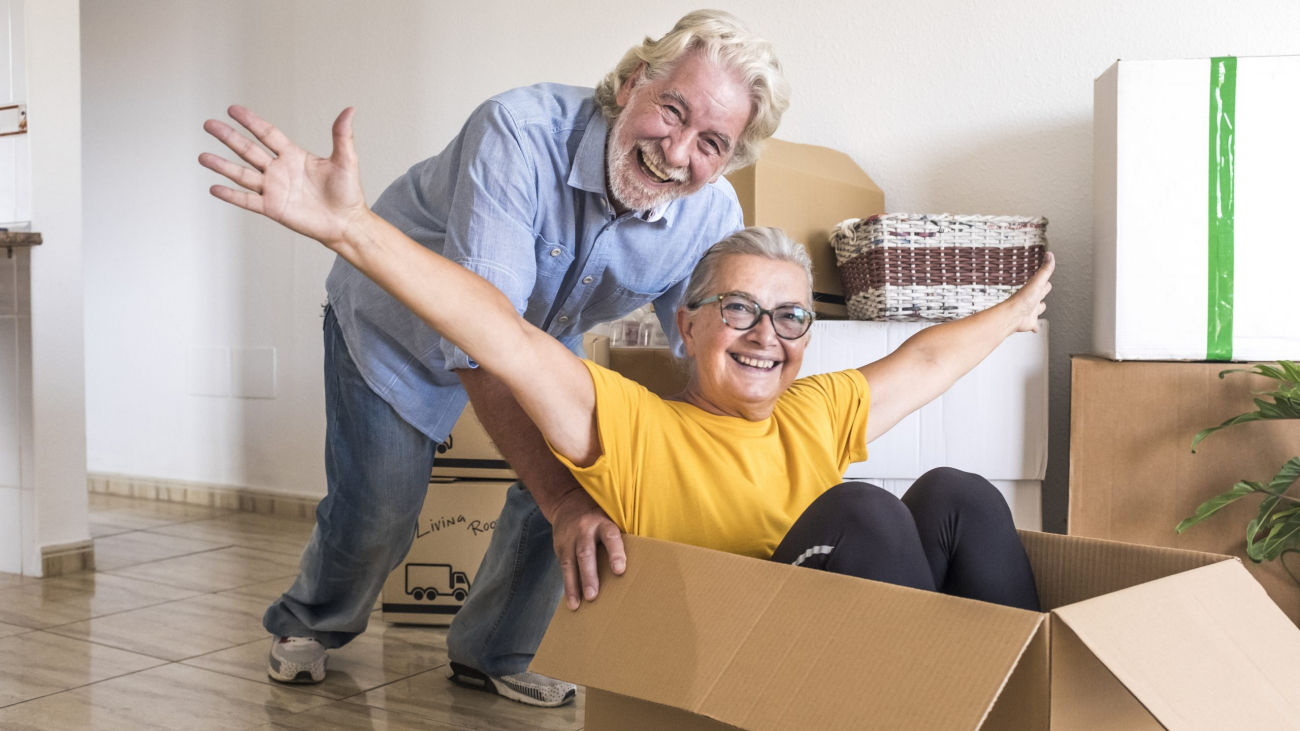 Happiness of two senior people in empty room playing like children in relocation happy for new beginning like retired with moving boxes on the floor