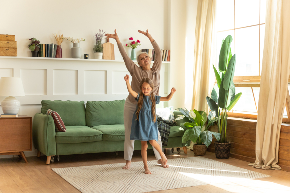 Happy little preschool child girl in dress spending active weekend time with grandmother. Energetic senior female grandma dancing together with granddaughter to music in living room.